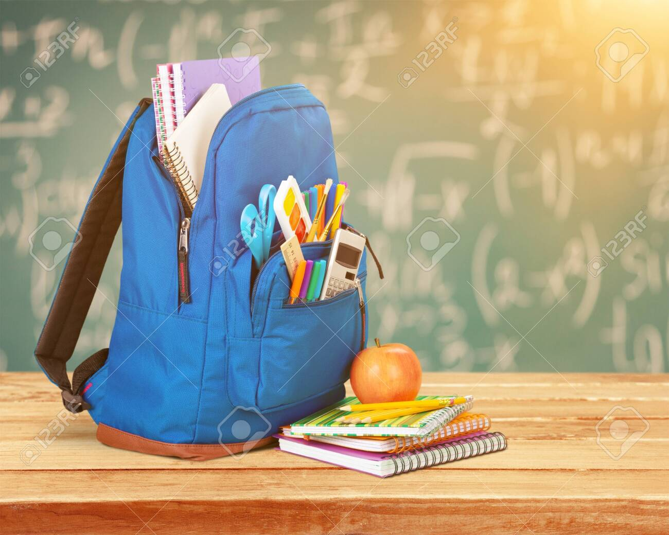 Open blue school backpack and notebook with apple - 125141397