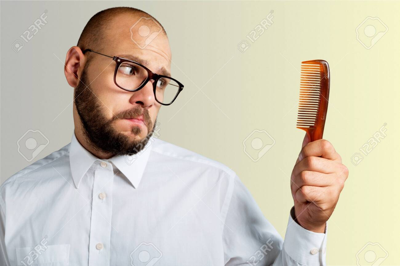 Man with black glasses holding comb on white wall - 125156435