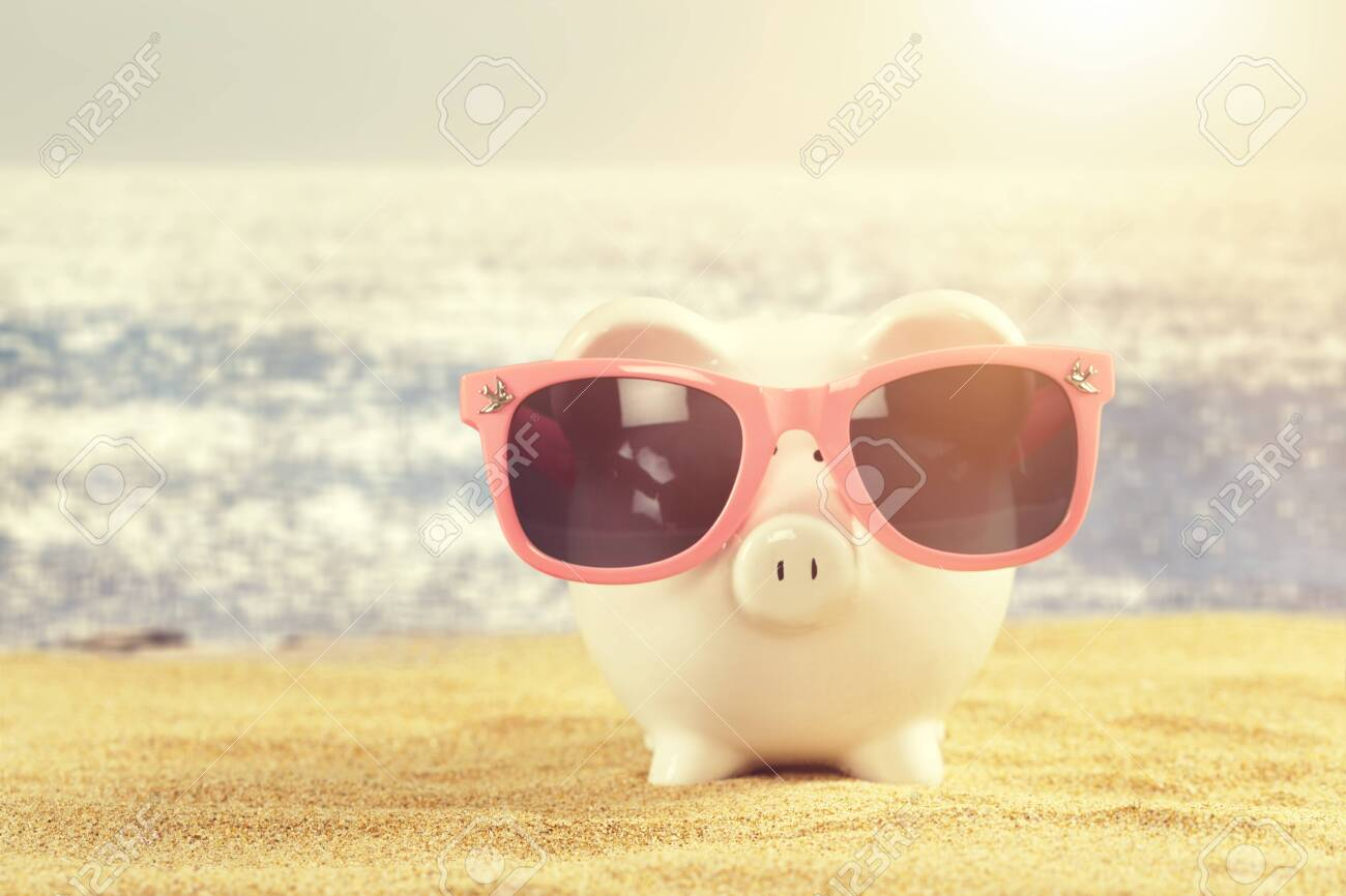 Summer piggy bank with sunglasses on the beach - 128656848