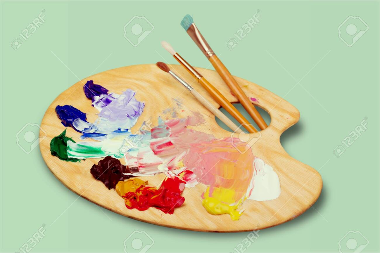 Wooden art palette with blobs of paint and a brushes on white background - 128026343