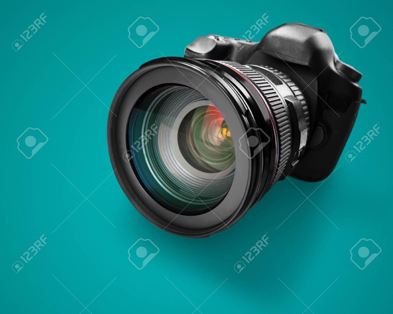 Black camera on green background - 128026993