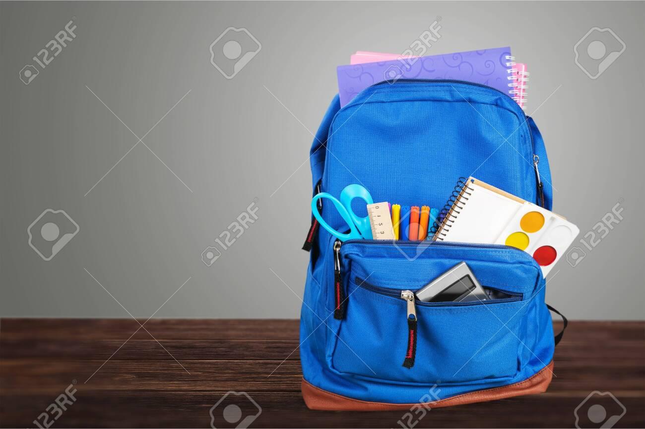 Open blue school backpack on wooden desk - 128027025