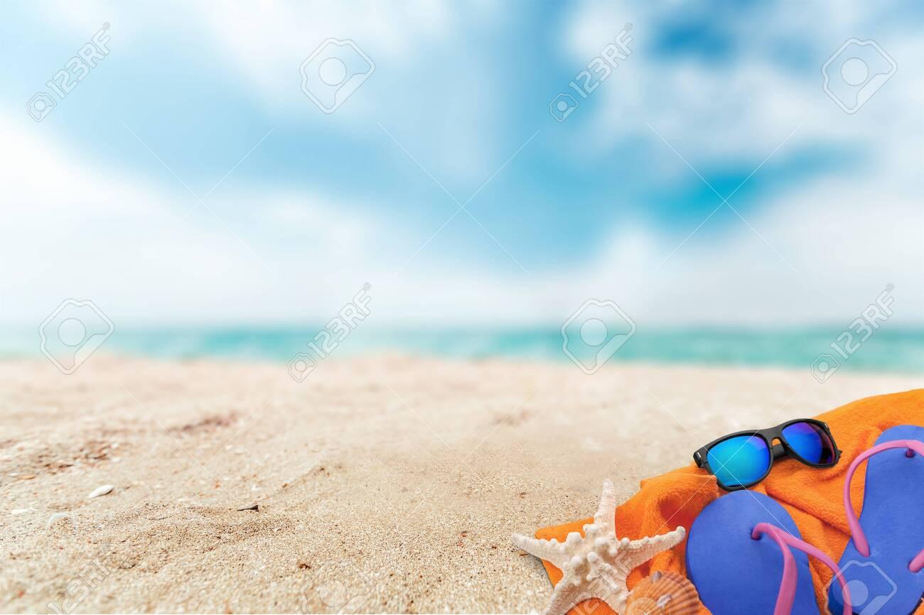 Straw hat, bag, flip flops on beach - 128032744