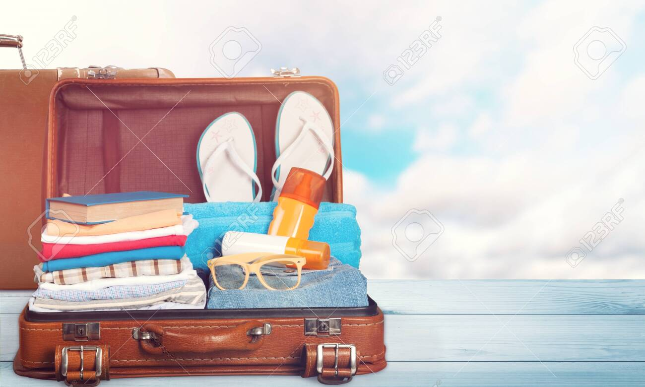 Retro suitcase with travel objects on sea background - 128531104