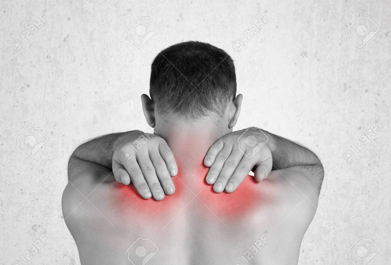 Back view of shirtless man touching his aching back - 128522339