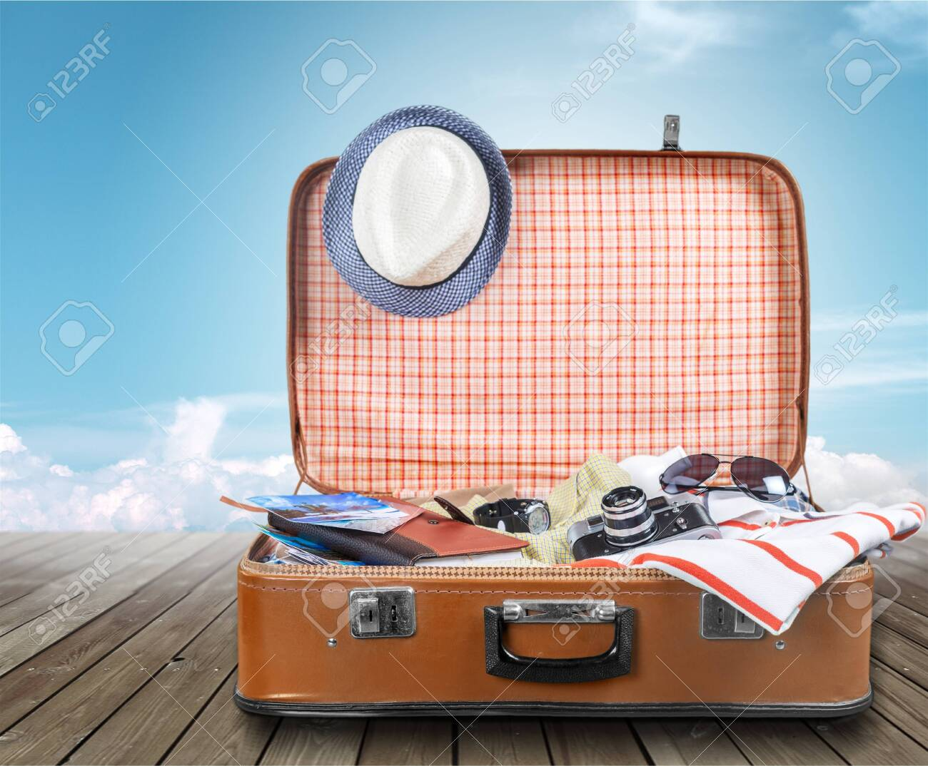 Suitcase with clothes and other travel accessories - 131983523
