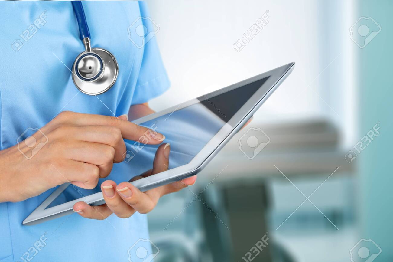 Doctor at hospital working with tablet - 129759133