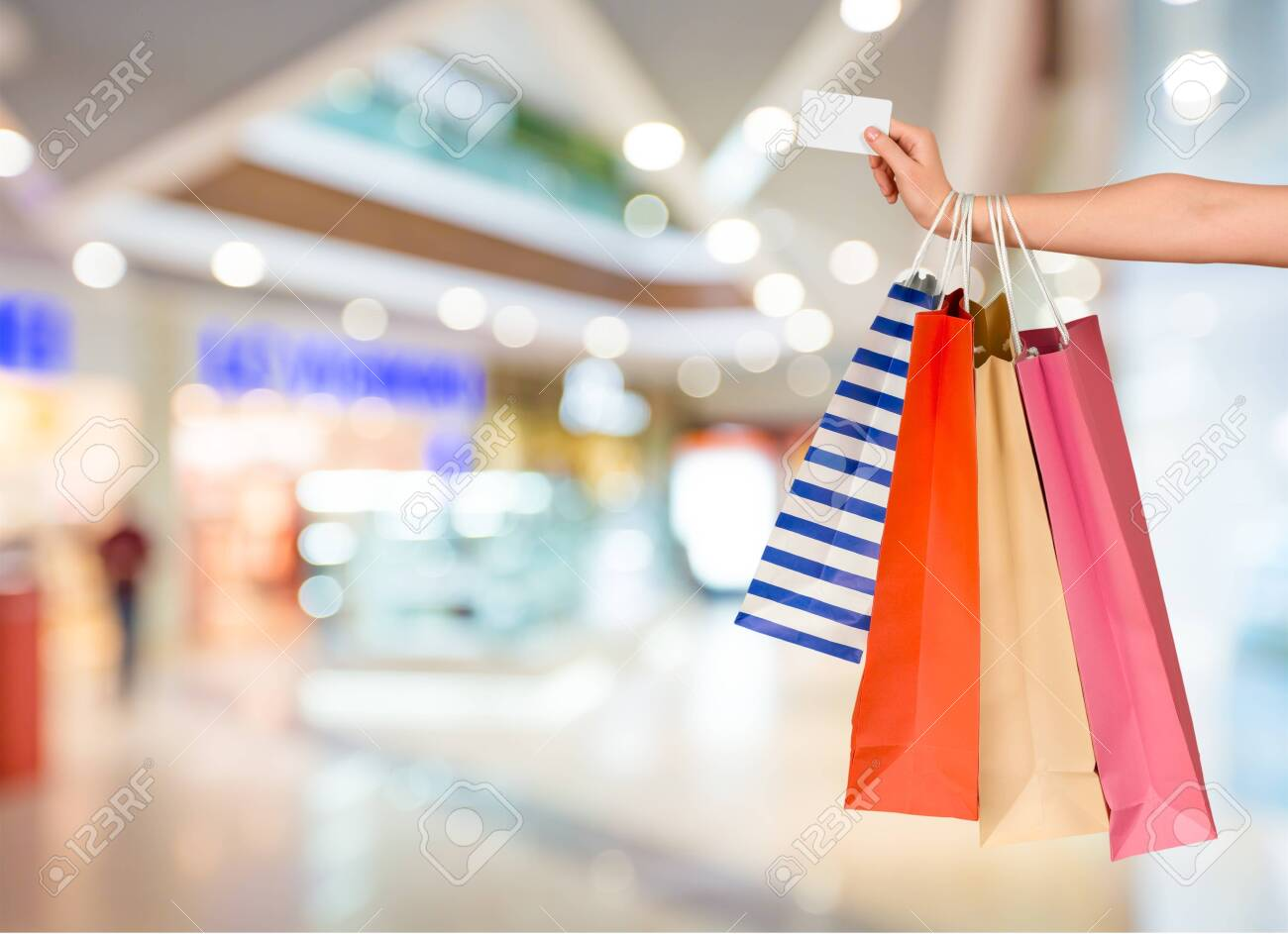 Close up woman hand with many shopping bags and credit card - 129955994