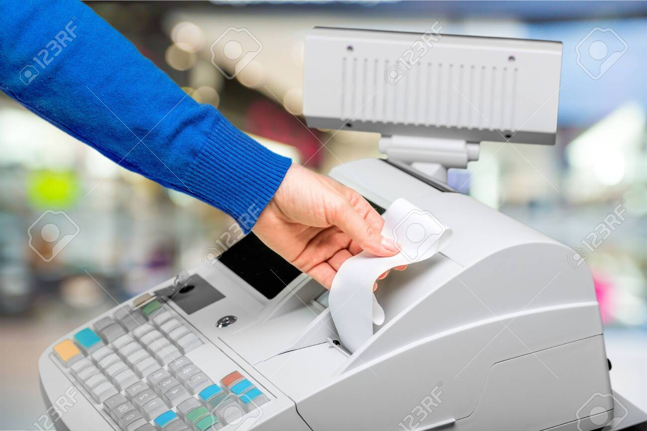 Cash register with LCD display and worker's hand holding receipt paper over blurred supermarket interor - 130158132
