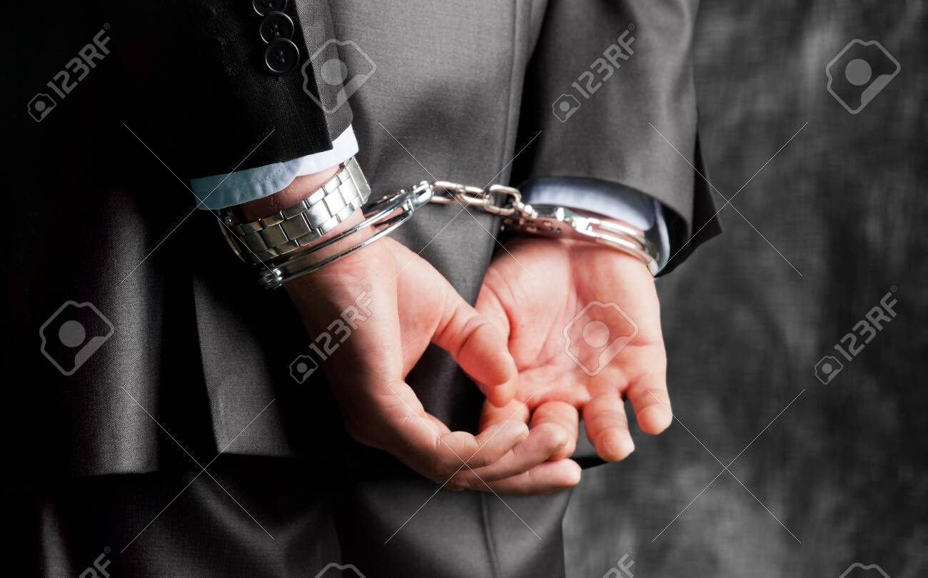 Cropped image of male hands in handcuffs behind his back - 133653641