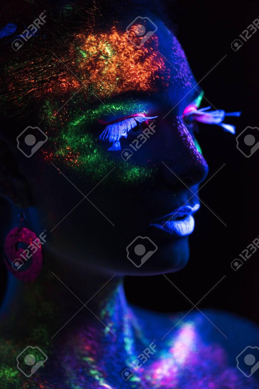 mujer sensual en maquillaje pintura mirando el lado pintura fondo oscuro foto