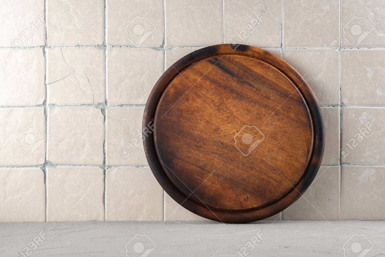 Cutting board on a kitchen background with ceramic tiles