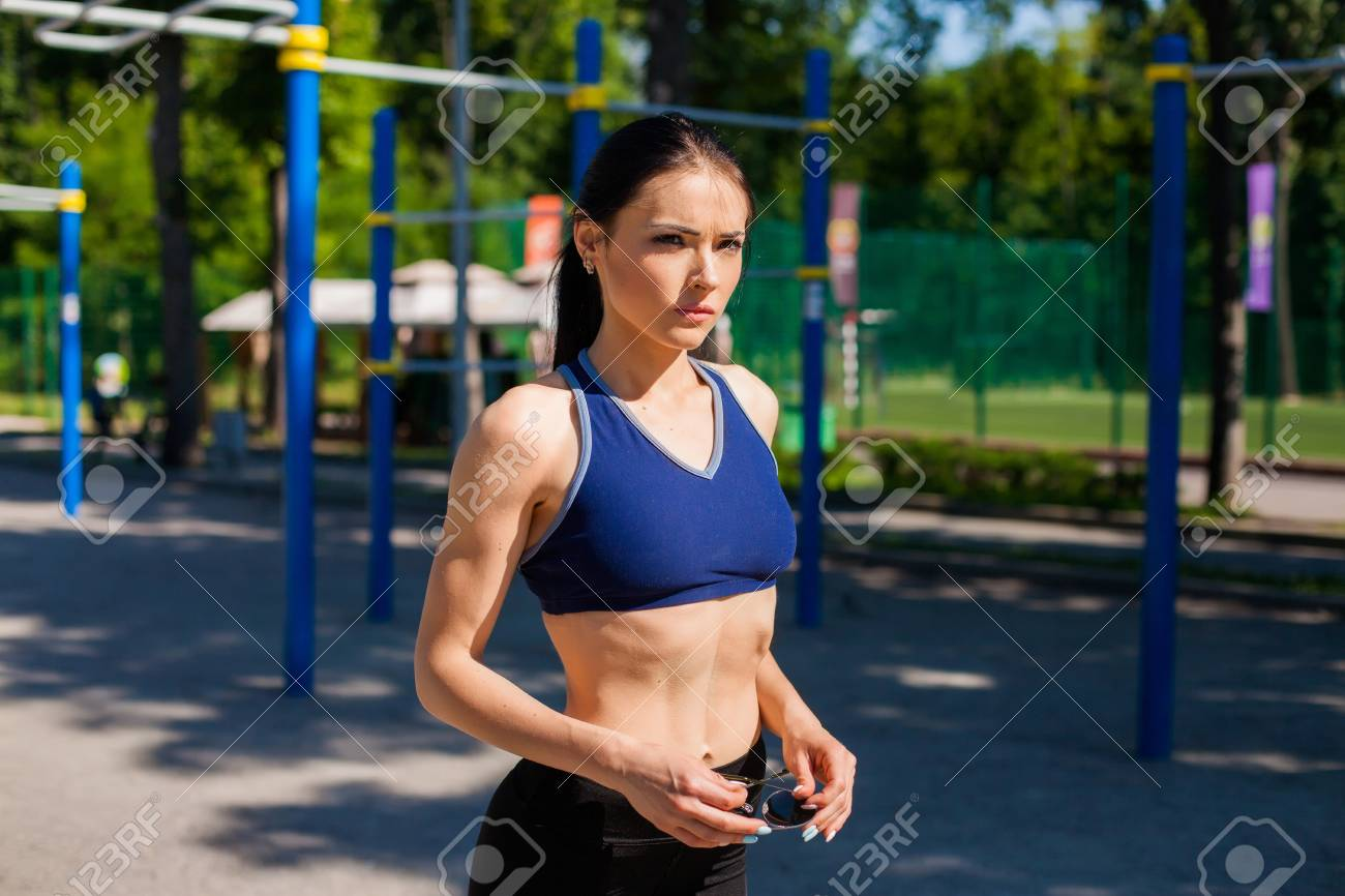 07b38924f1dde Stock Photo - Young sportive teen in a bright blue sport bra and black  leggings on the sport playground. Photo of an athlete girl with a beautiful  sports ...