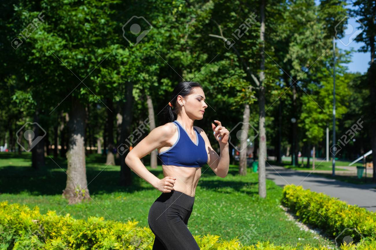 08c837d956be7 Stock Photo - Young sportive teenager in a bright blue sport bra and black  leggings running along the path in park. Photo of an athlete girl with a ...