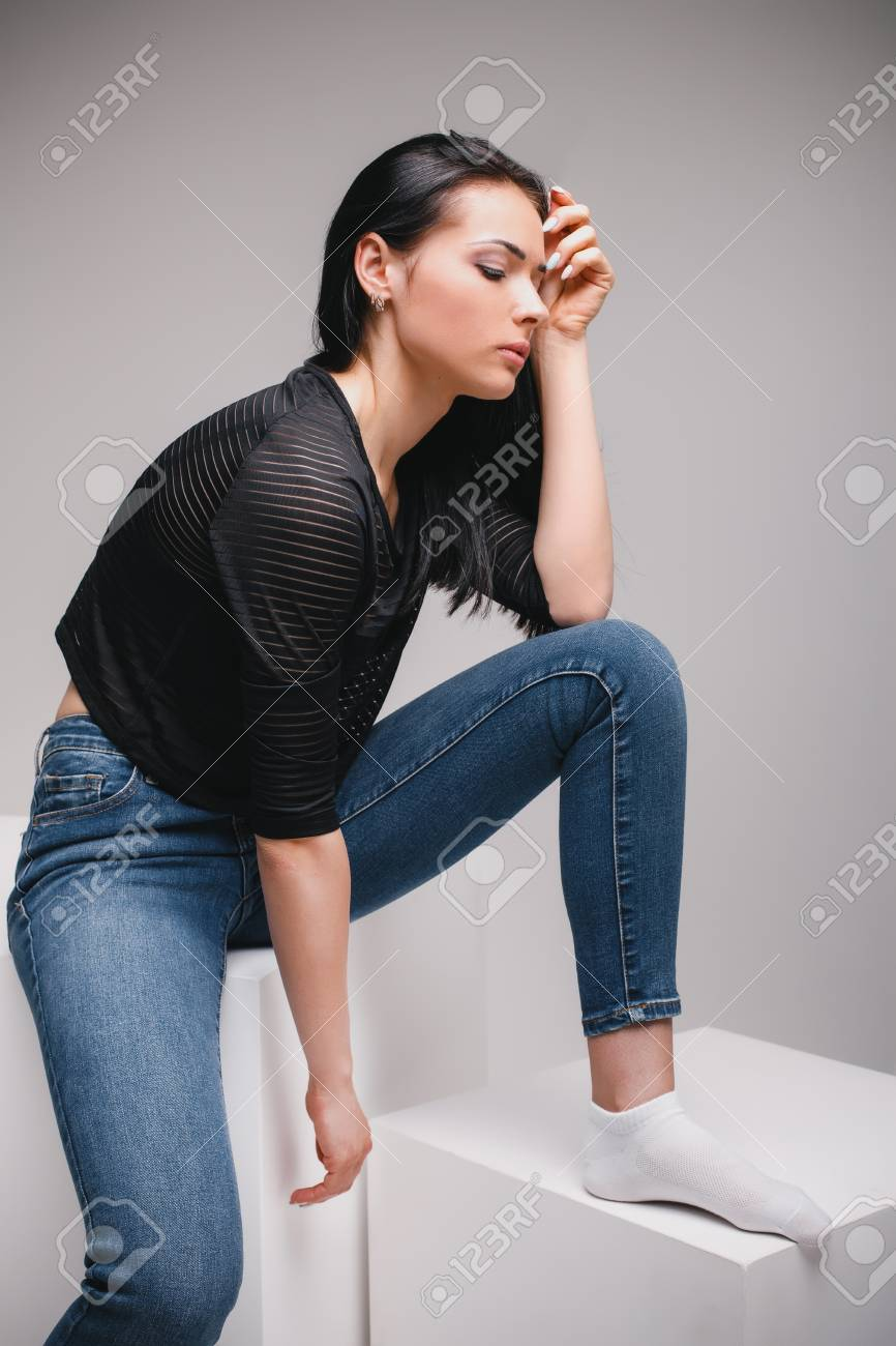 4d7f97ec beautiful woman in black shirt and jeans sitting on cube in photostudio on gray  background Stock