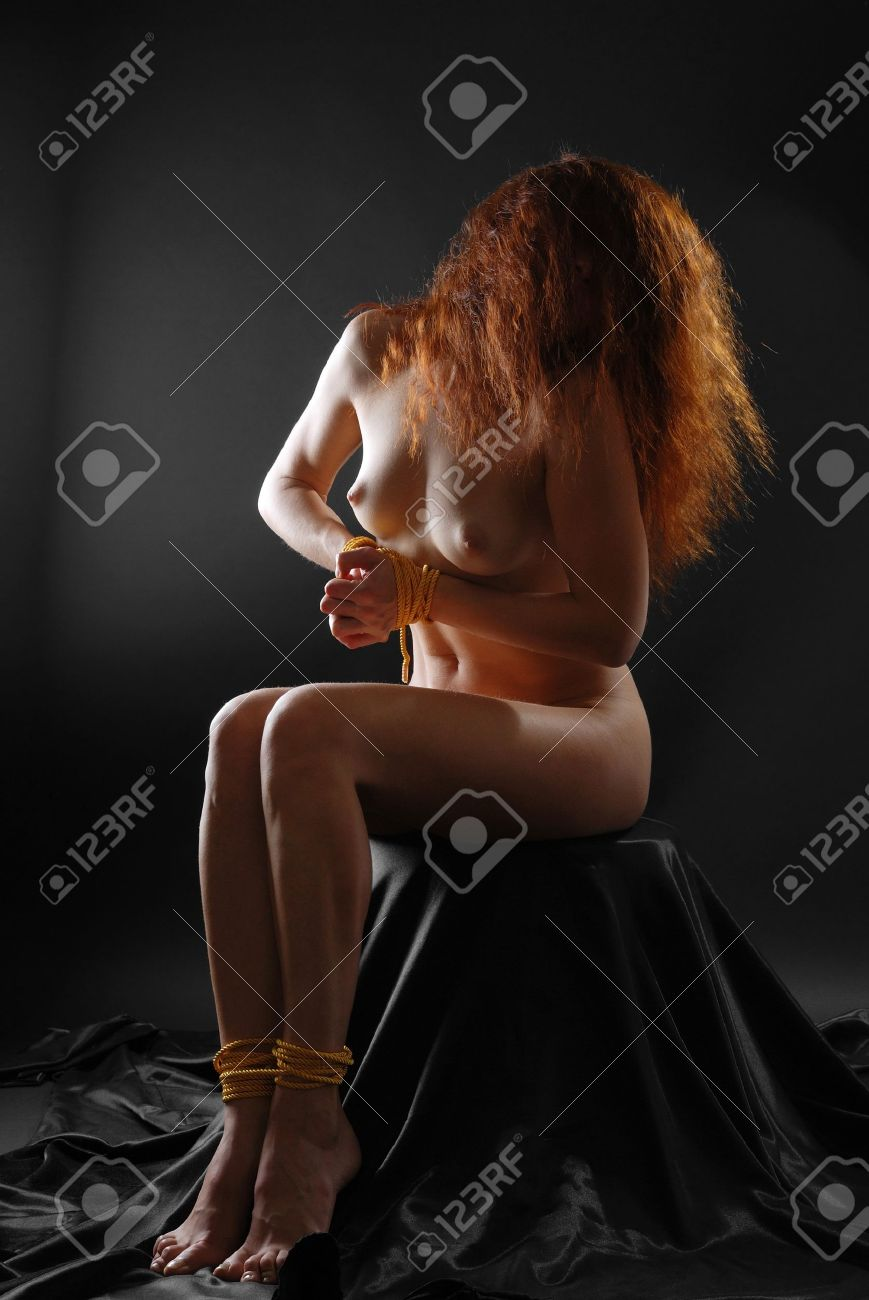 Naked woman sitting with bound hand and foot, low key Stock Photo - 4403992