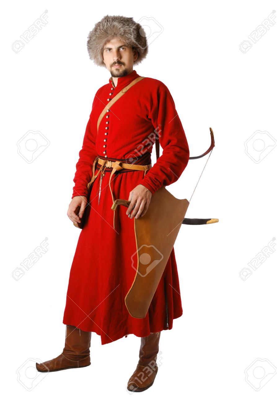Young man is wearing vintage uniform of Tatar warrior of 17th century. Bearded re-enactor is armed with a saber and a bow. He is dressed in red caftan, fur cap. He is member of Society of Historical Reenactment. Stock Photo - 5979252