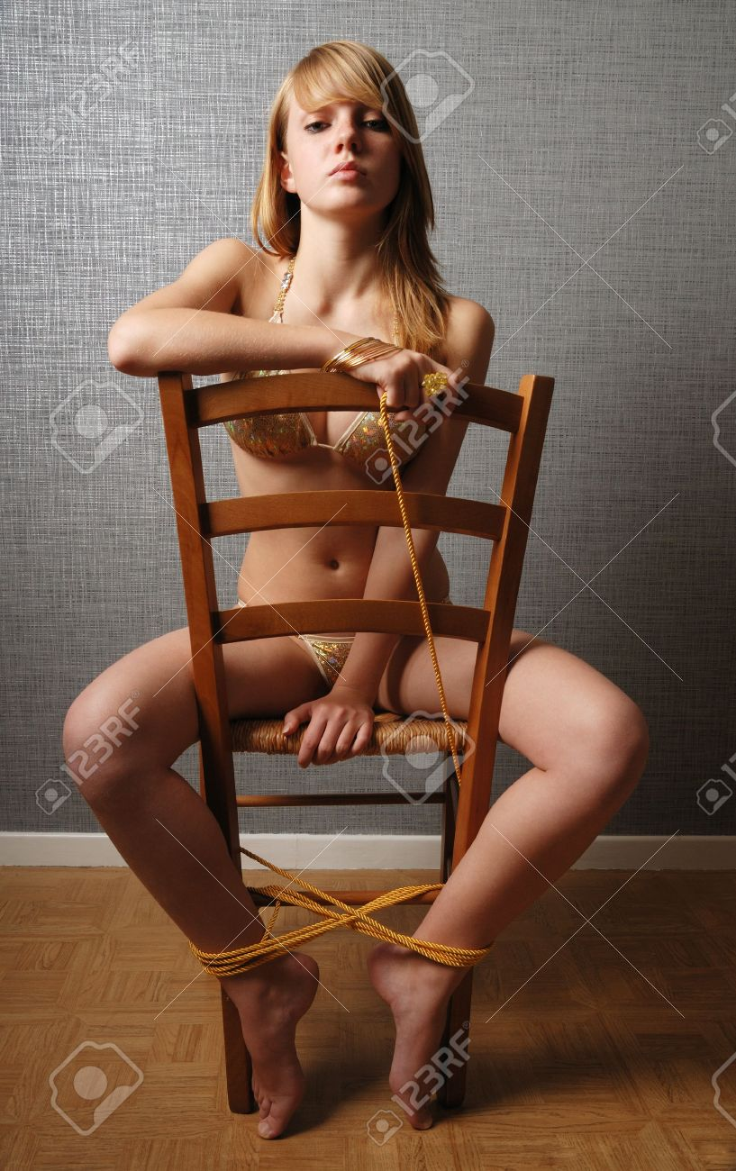 Teenage girl is straddling on the chair. She is wearing bikini. Her legs are bound to the chair. She holds the end of rope and looks at the camera calmly. Stock Photo - 6221946