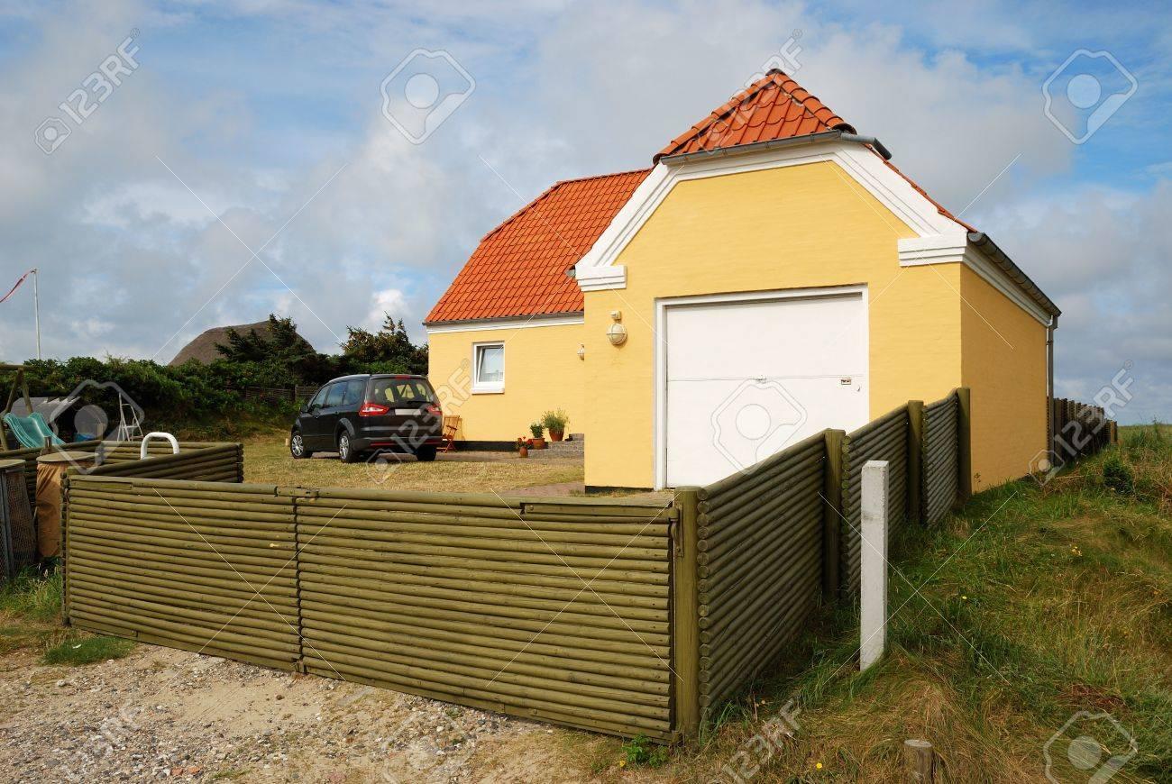 il ya une maison moderne, un garage et une voiture dans la cour