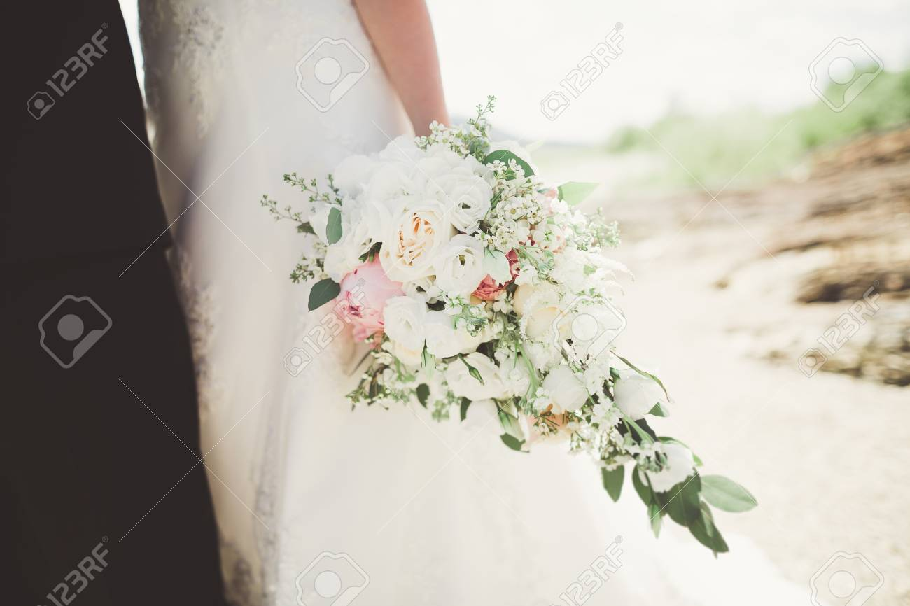 Pretty Good Wedding Bouquet Of Various Flowers In Hand Stock Photo