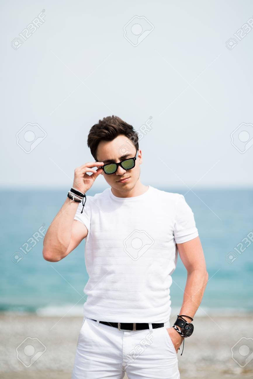 5333e9bec0d2 Portrait of young man in sunglasses smiling on the beach Stock Photo -  87534372
