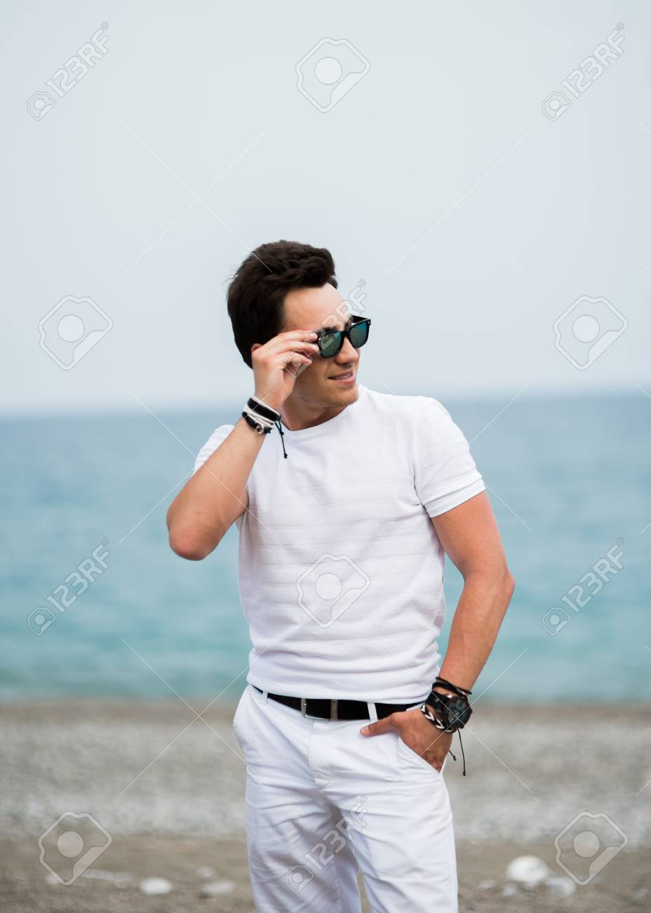 e80bd317d882 Portrait of young man in sunglasses smiling on the beach Stock Photo -  87534373