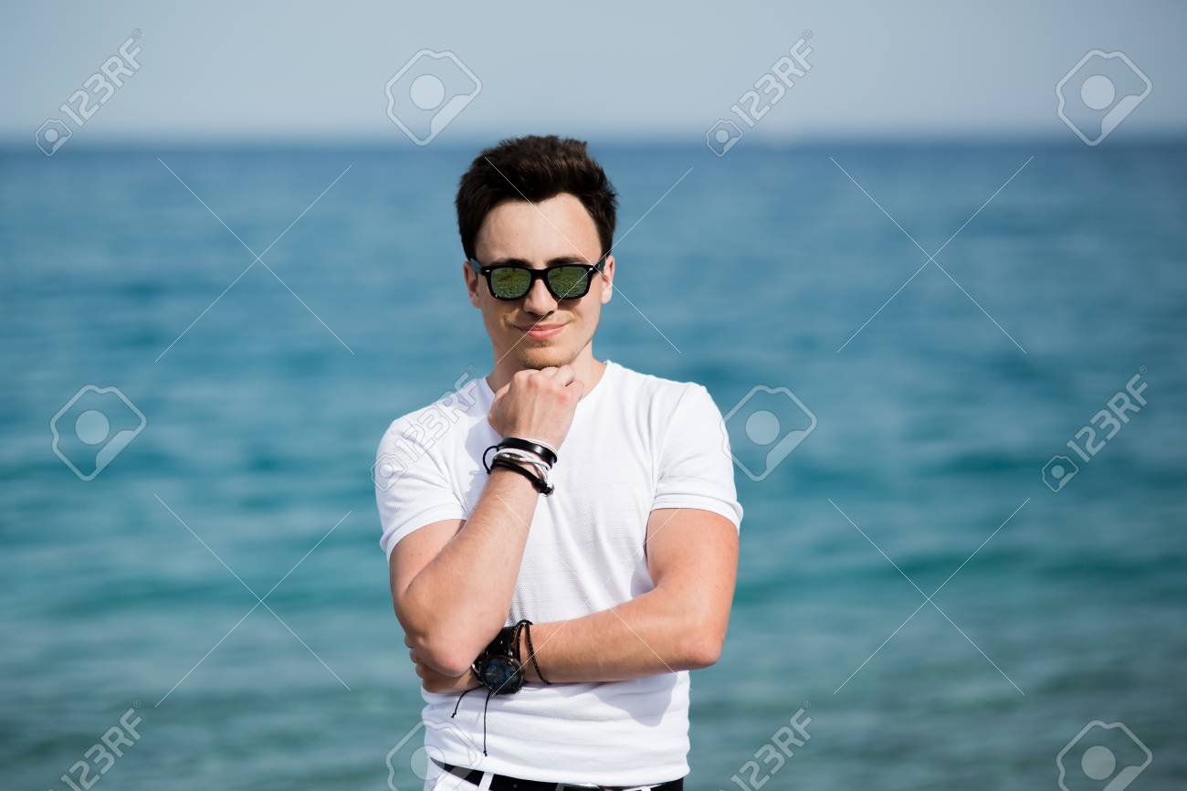d7ae2bd86fec Portrait of young handsome man in sunglasses smiling on the beach Stock  Photo - 88112166
