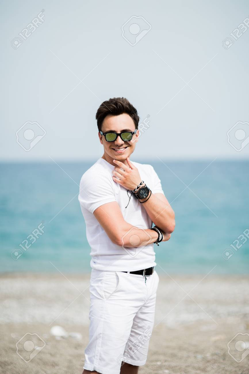 7579d730d45a Portrait of young man in sunglasses smiling on the beach Stock Photo -  91104168