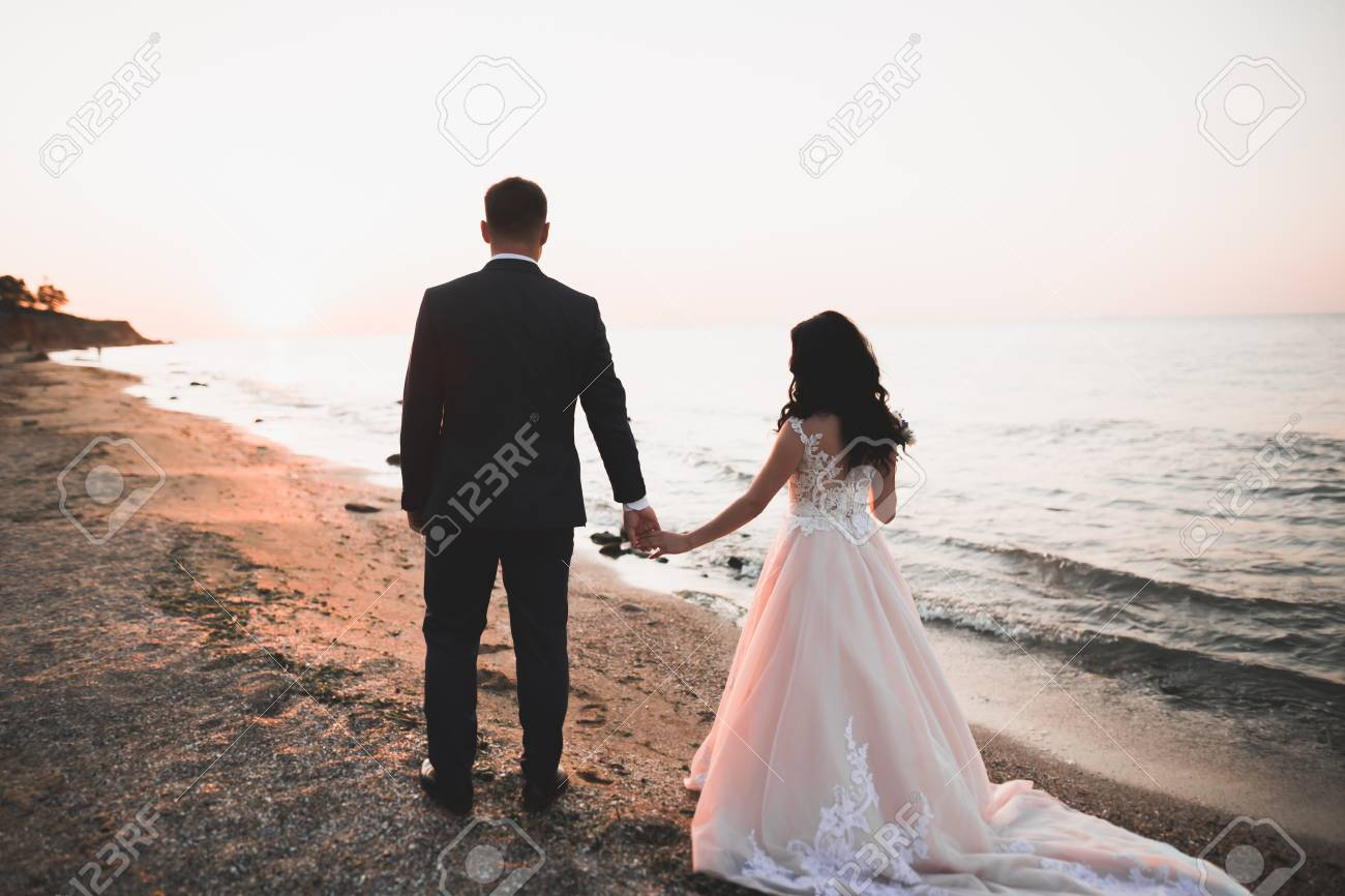 Happy and romantic scene of just married young wedding couple posing on beautiful beach. - 121556915