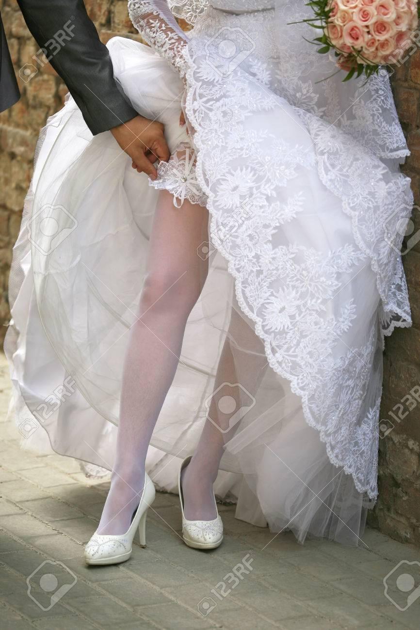 the groom adjusts bride's wedding garter - 52069615