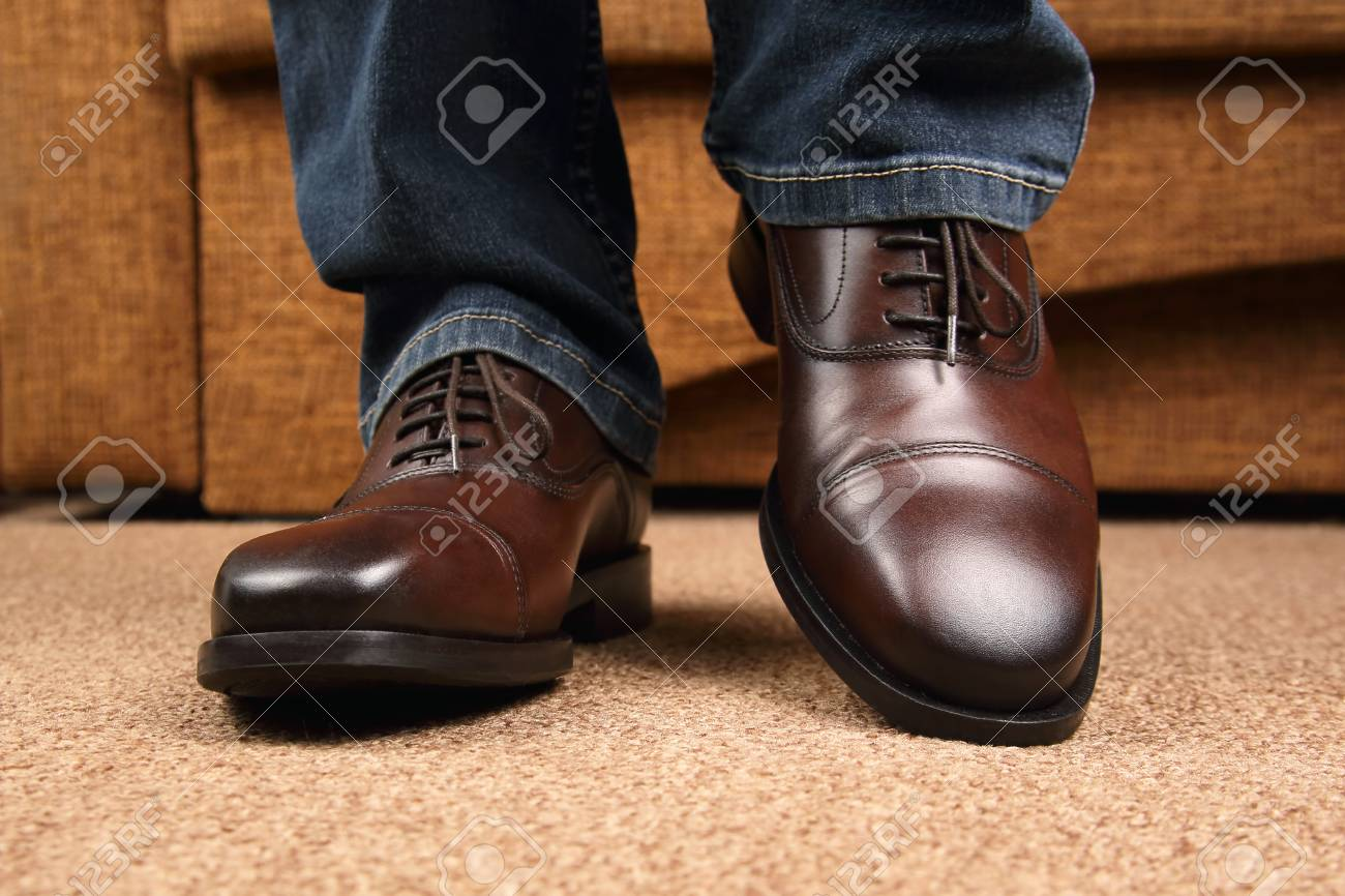 Men\u0027s legs in jeans shod in classic brown Oxford shoes