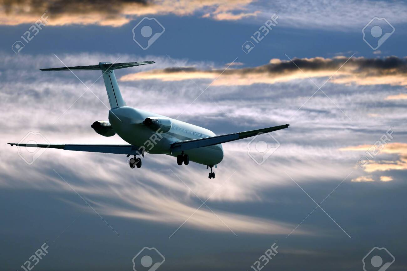 passenger jet plane flying in the evening sky at sunset. commercial airline - 123915907
