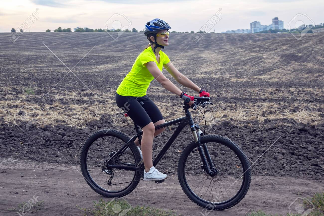 Beautiful girl cyclist rides a bicycle on the field. Healthy lifestyle and sport. Leisure and hobbies - 145986577