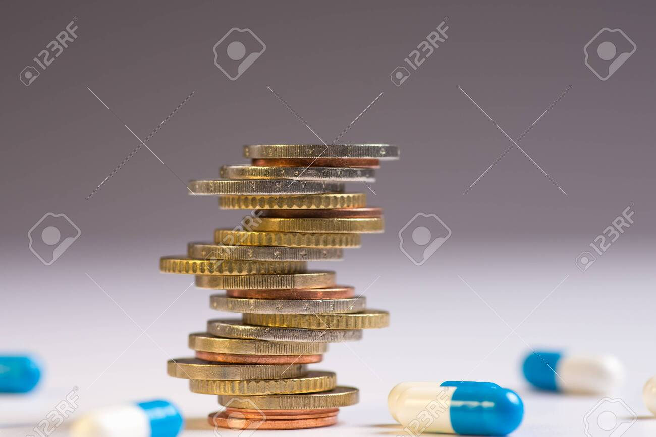 Coins are placed among themselves in different positions next to the blue and white pills. Copy space for text - 121651477