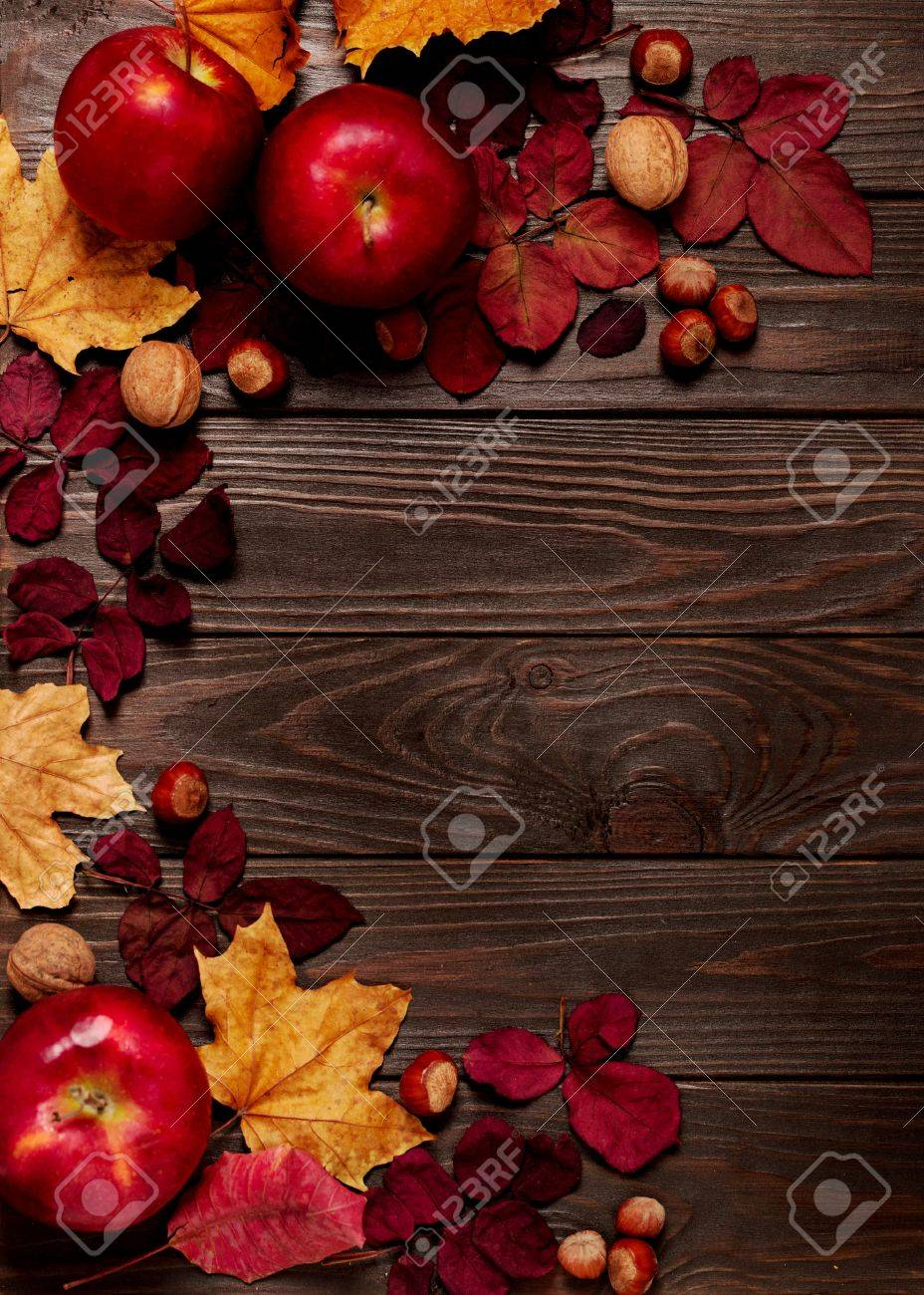 Flat lay frame of autumn crimson and yellow leaves, hazelnuts, walnuts and apples on a dark wooden background. Selective focus. - 83530998