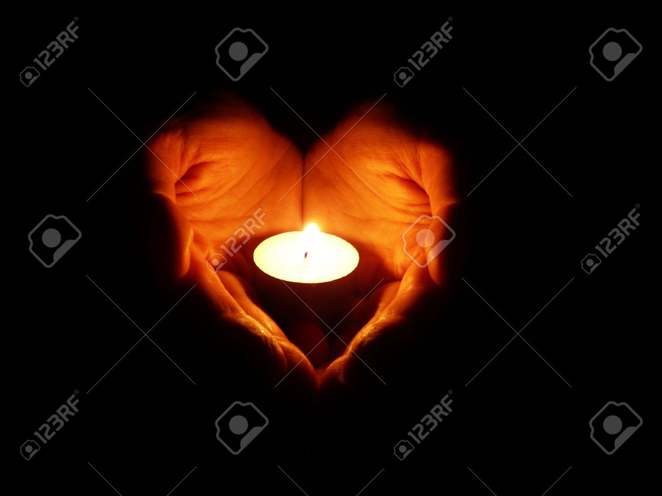 heart-shaped hands holding one candle in darkness Stock Photo - 1171287