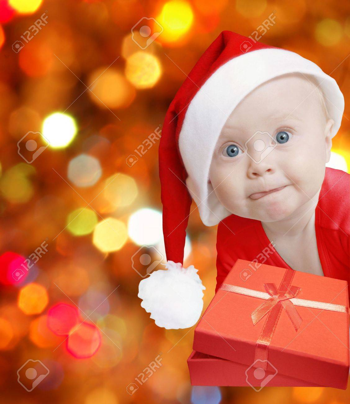 funny baby in Santa hat with present box on bright festive background, space for text Stock Photo - 3868508