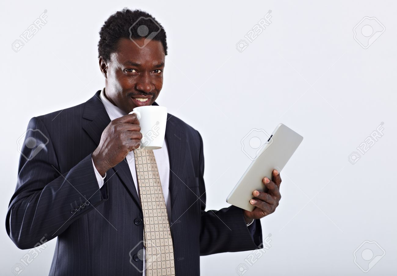 Handsome African American business man with cup of tea and tablet pc Stock Photo - 9067861