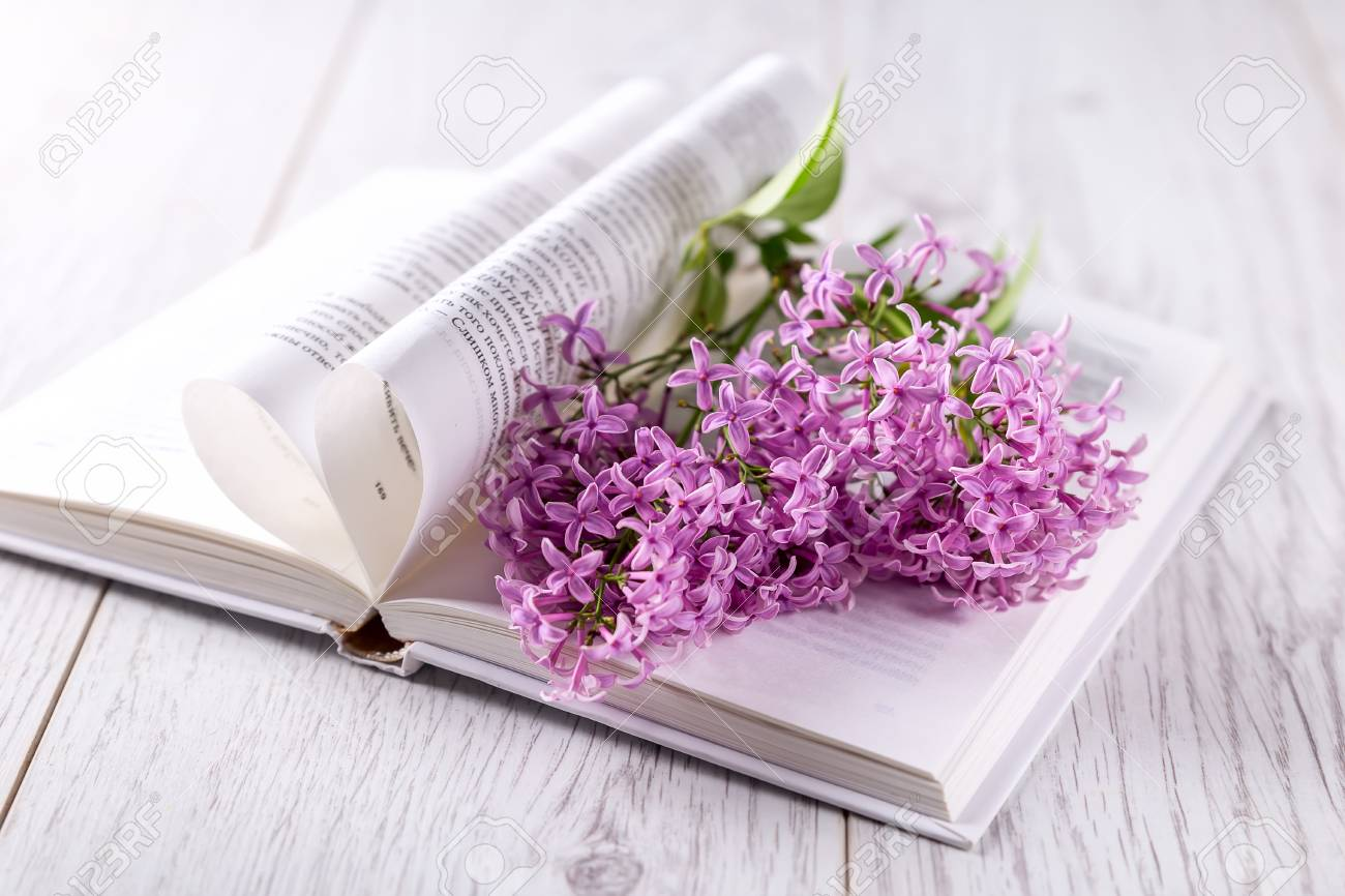Lilac Flowers On The Book An Open Book On The Table Flowers