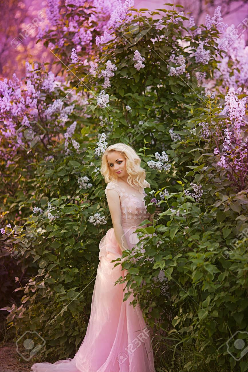 Beautiful woman enjoying lilac garden young woman with flowers beautiful woman enjoying lilac garden young woman with flowers in green park cheerful teenager izmirmasajfo