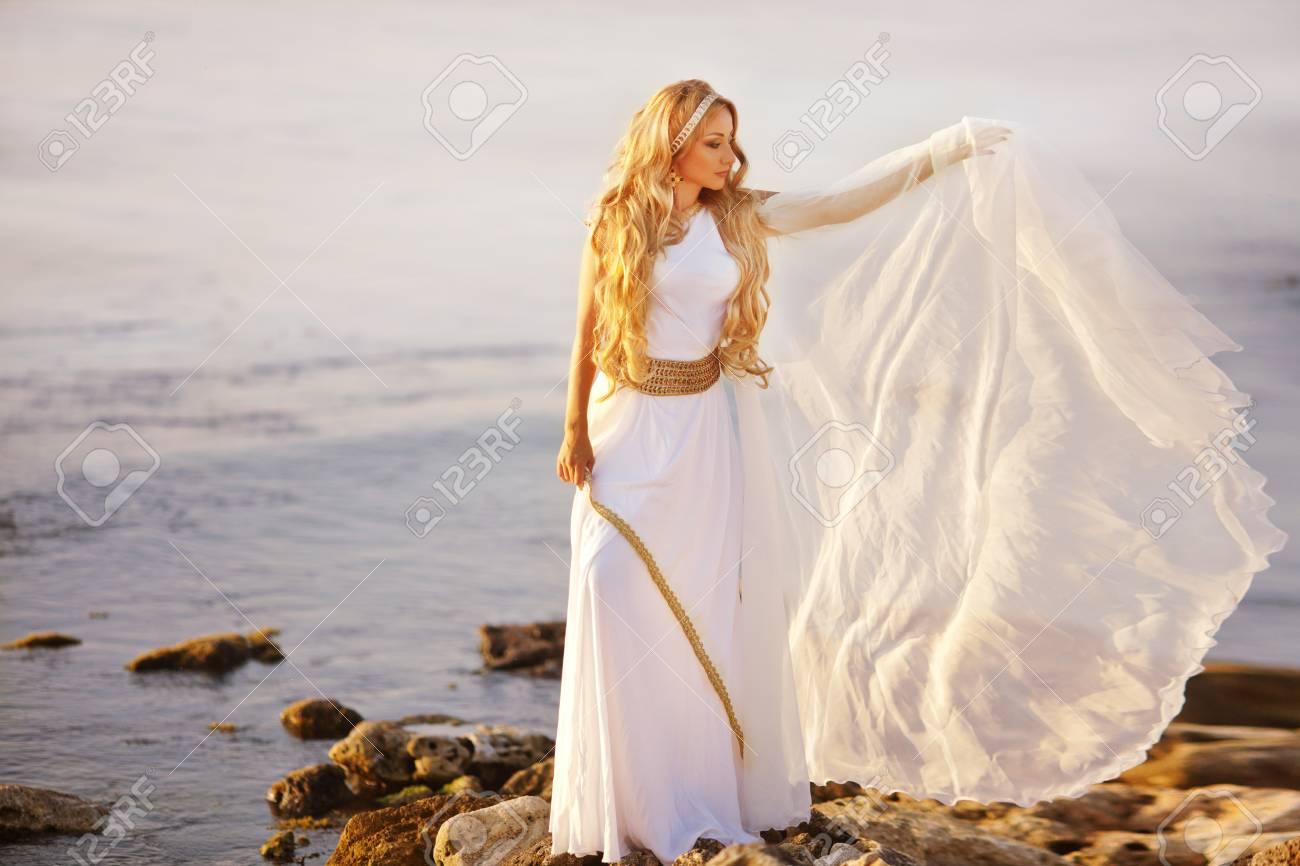 Beautiful Girl In A Long White Wedding Dress In Greek Style Is ...