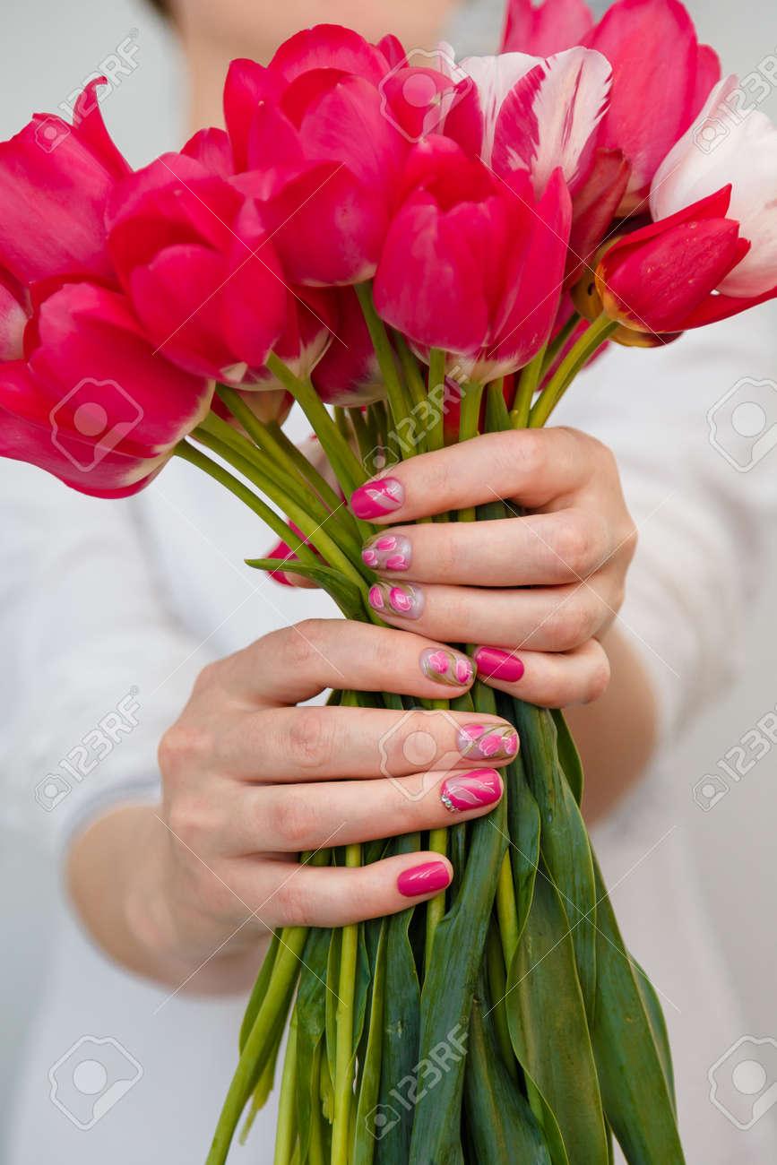 153307845 woman holding tulips bouquet spring manicure nail art flowers design concept vertical shot close up