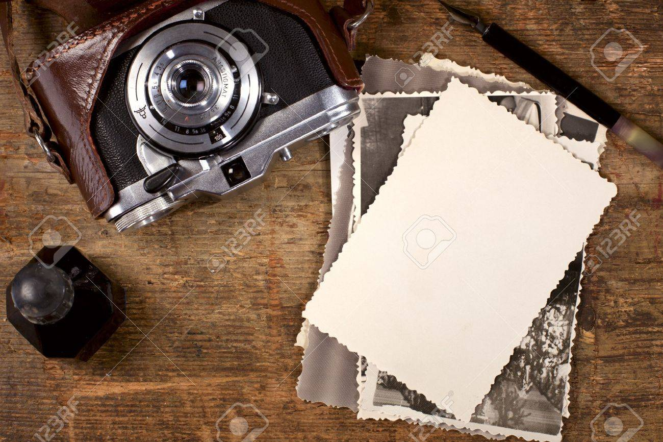 vintage ink and  pen, old photos and camera on old wooden table Stock Photo - 9522870