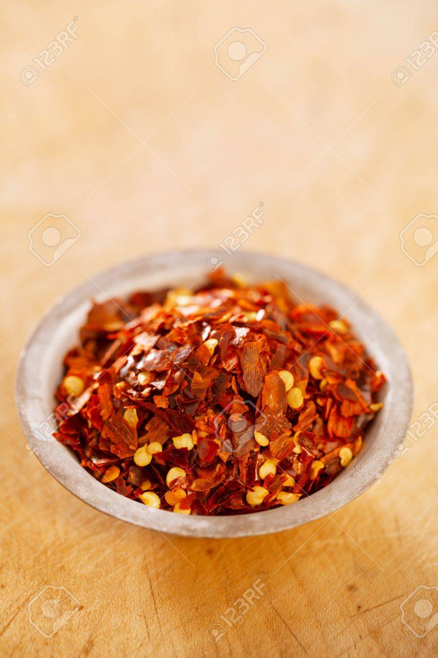 Hot Red Chilli Chillies pepper crushed in tin bowl on wood Stock Photo - 14772182