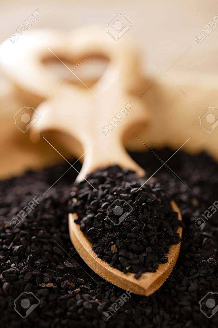black cumin or caravay or onion seeds in heart shape wooden spoon Stock Photo - 15408614