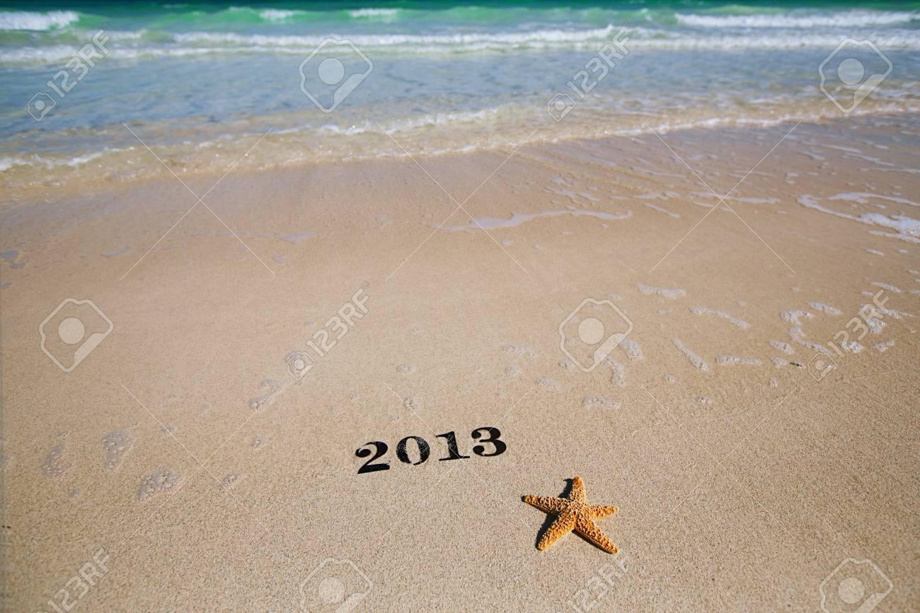 2013 new year metal numbers on beach sea sand, shallow DOF Stock Photo - 17229661