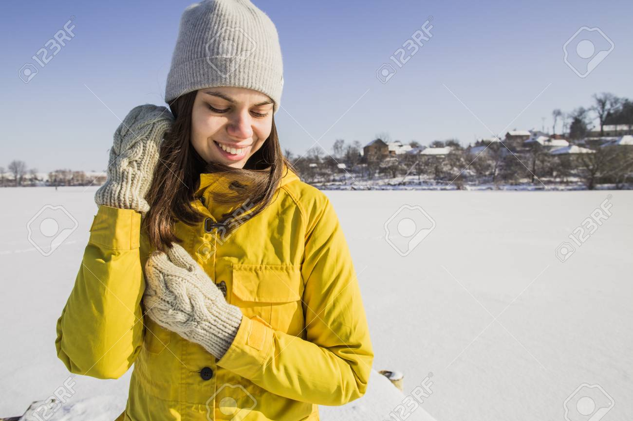 340fd5101f6 Stock Photo - Young pretty girl in a yellow coat and grey hat standing near  winter lake. Outdoor photo.
