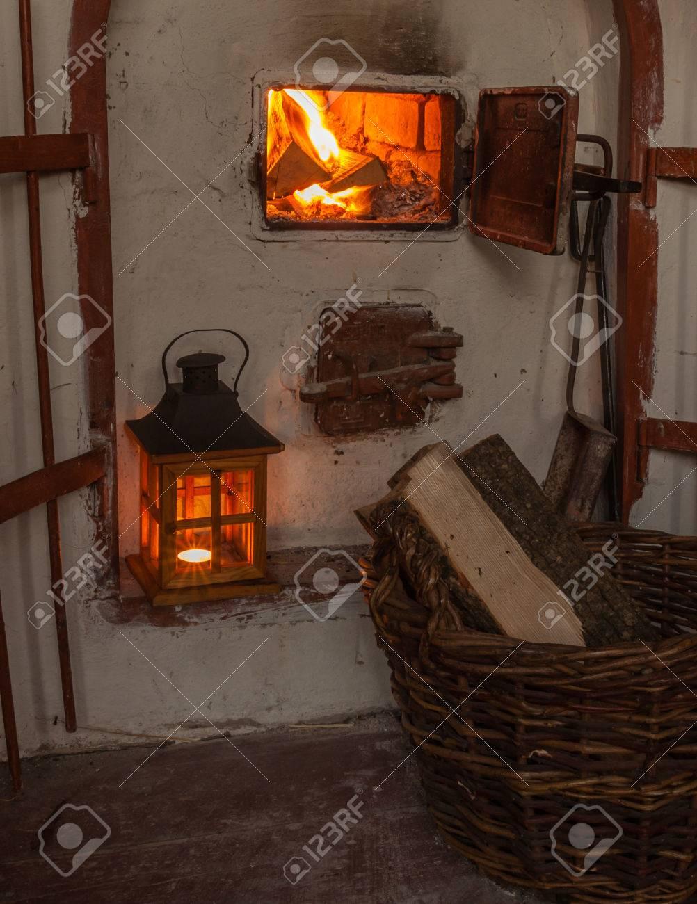 lantern near an open fireplace and a basket of firewood stock