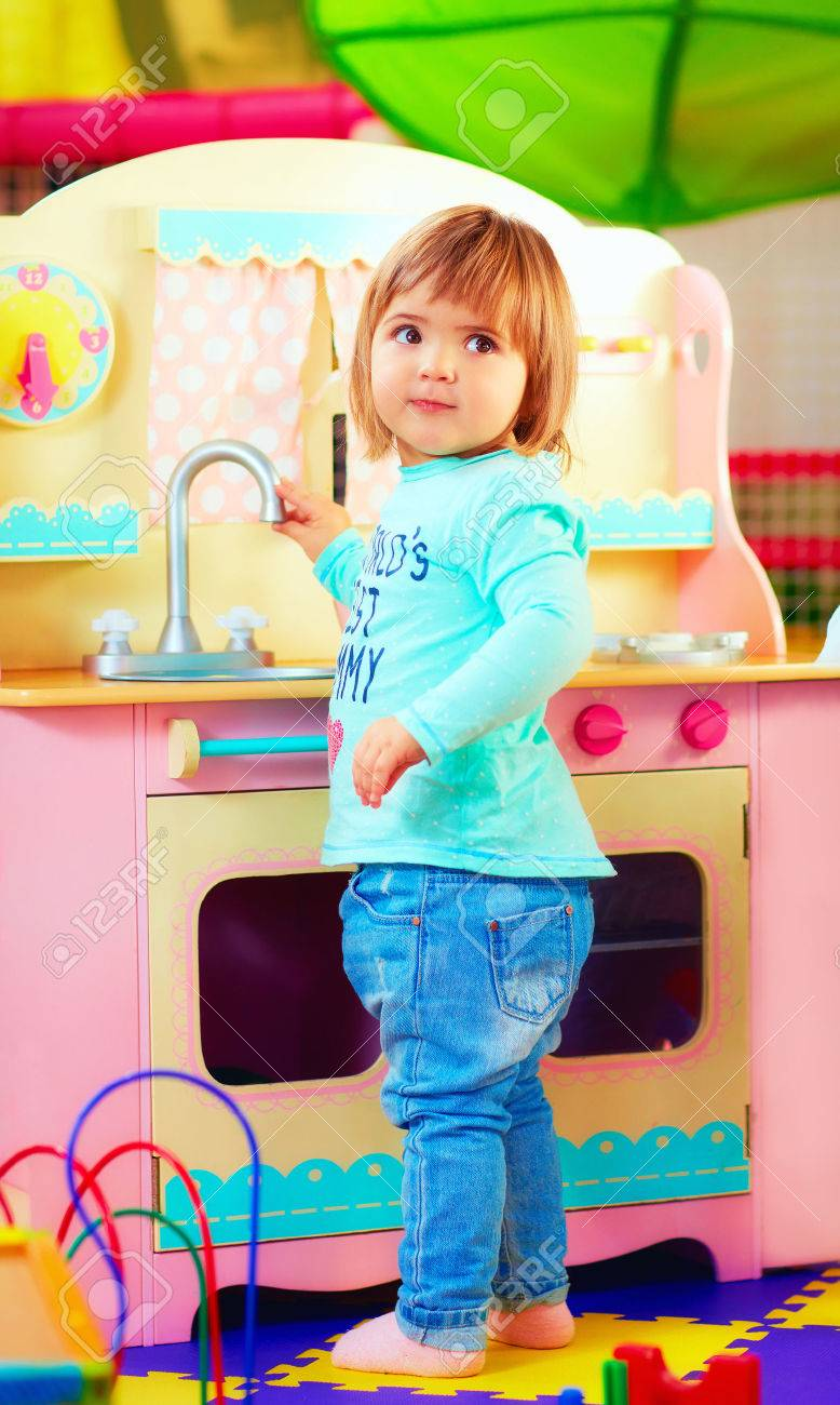 Cute Little Girl Playing With Toy Kitchen In Kindergarten Stock ...