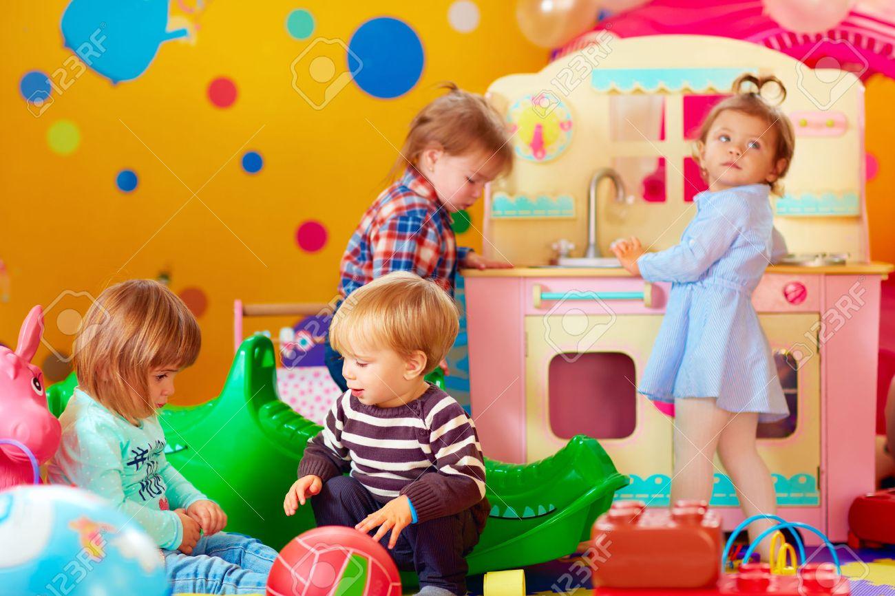 Lindos Niños Pequeños Juegan Con Los Juguetes En El Grupo Cuarto De ...
